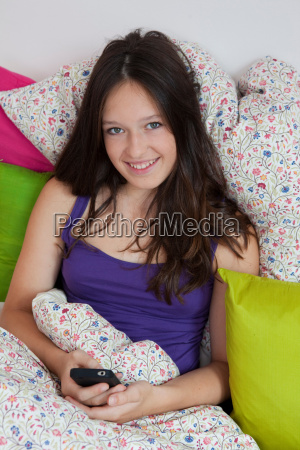 smiling girl using cell phone in