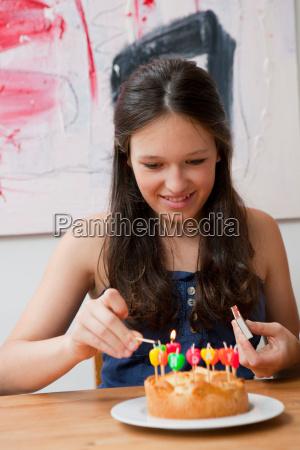 girl lighting candles in birthday cake