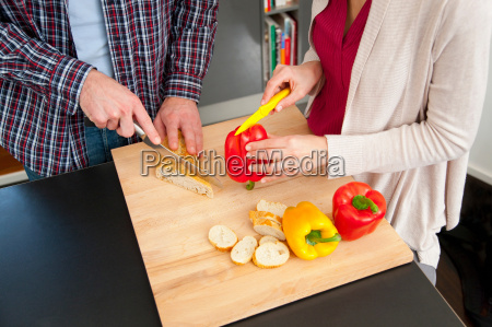 couple chopping food in kitchen
