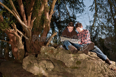 boys reading map on rock formations