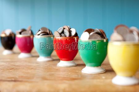 egg cups full of money on