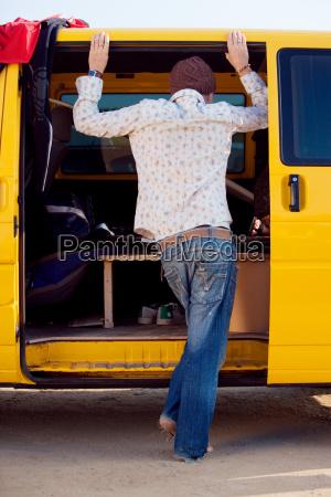 man standing in van doorway looking