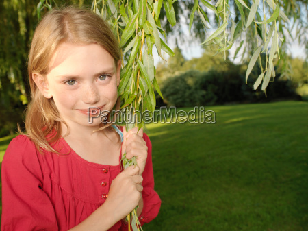young girl pulling on branch