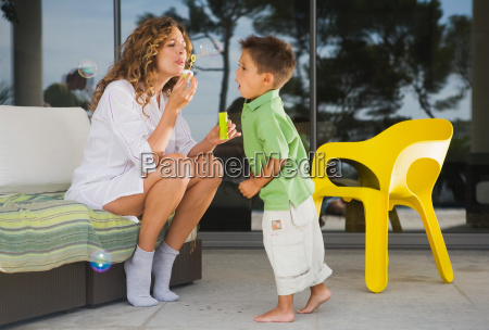 woman and boy blowing bubbles