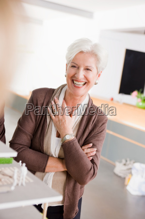 woman at a architecture model smiling