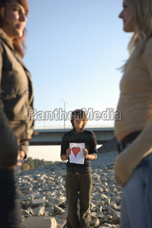 boy holding paper heart looking at