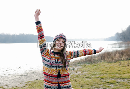 young woman outdoors stretching arms