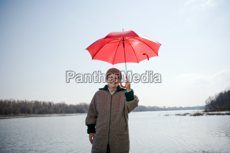 senior woman holding red umbrella