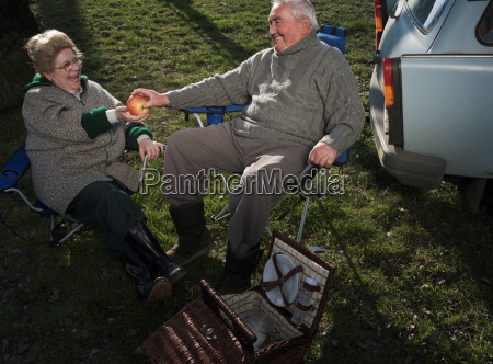 senior couple having picnic by car
