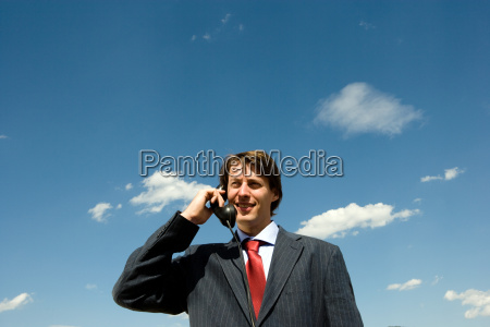 man holding old phone against blue