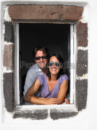 couple looking through window smiling