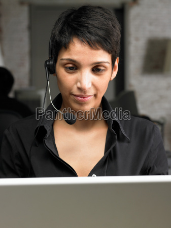 businesswoman wearing headset on lap top
