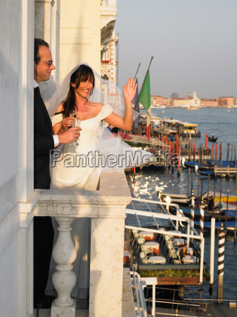 bride and groom on balcony toasting