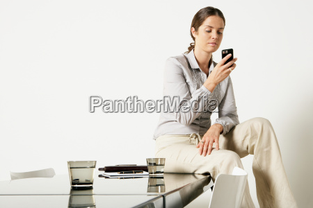 young business woman seated on desk