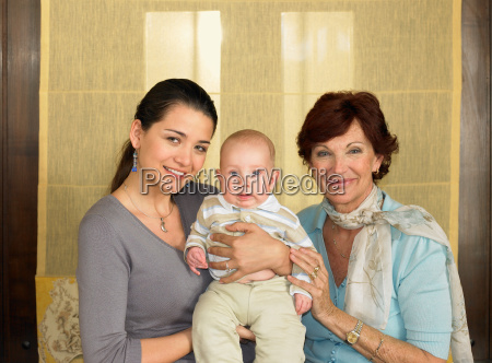 mother and grandmother holding baby boy