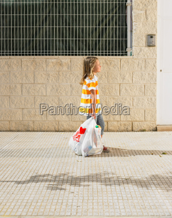 young girl walking on pavement