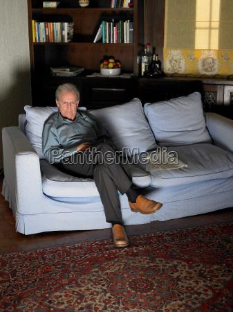 senior adult man sitting on sofa
