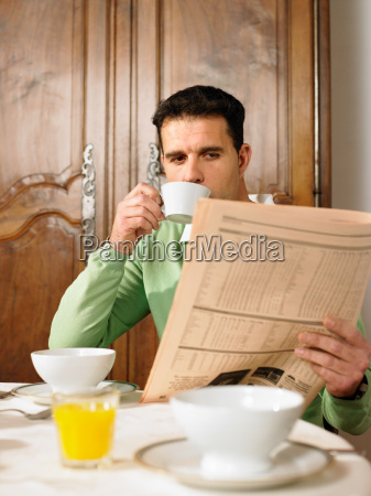 man reading paper at breakfast table