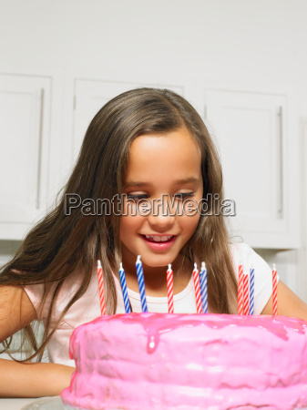 girl 8 10 looking at cake
