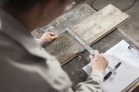 carpenter measuring wood plank with vernier