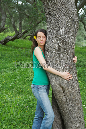 young woman hugging tree in orchard