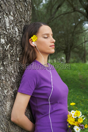 woman holding flowers leaning on tree