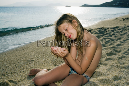young girl sitting on the beach