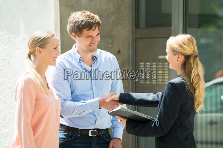 estate agent shaking hands with young