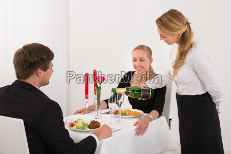female waitress pouring champagne into glass
