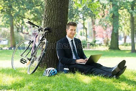 geschaeftsmann mit laptop im park