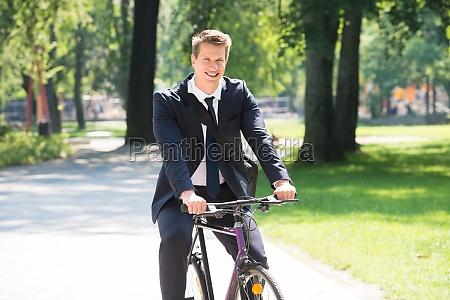 geschaeftsmann reiten fahrrad im park