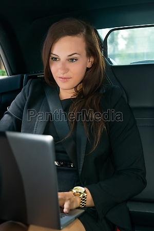 geschaeftsfrau mit laptop im auto