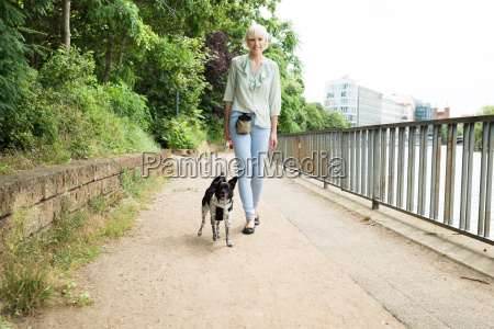 happy woman walking with her dog
