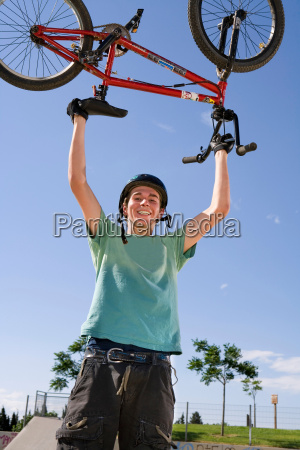 teen boy carrying bike over his
