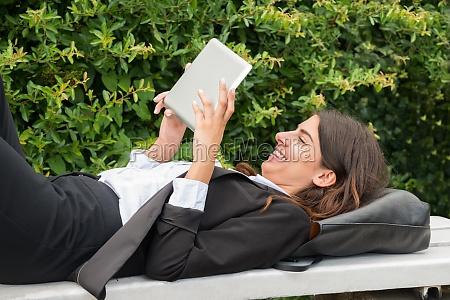 geschaeftsfrau sitzt auf bank im gespraech