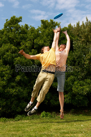couple jumping to catch a frisbee
