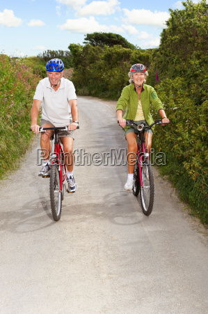 senior couple cycling on country lane