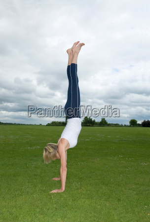 woman in park doing handstand