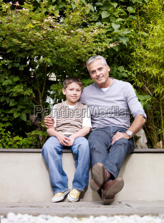 father and son sitting outside in