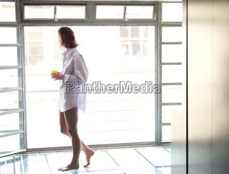 woman walking past window in morning