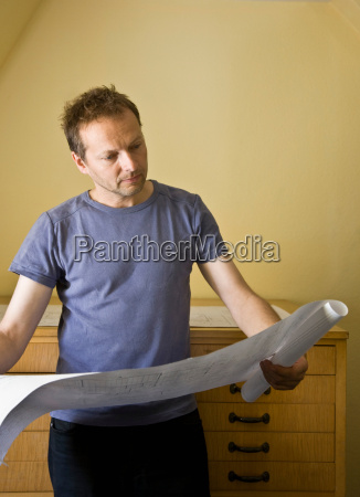 man looking over blue prints