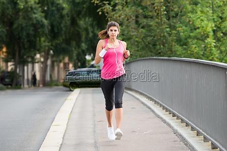 athlete woman running on sidewalk