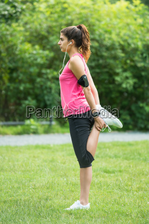 young woman doing exercise in park