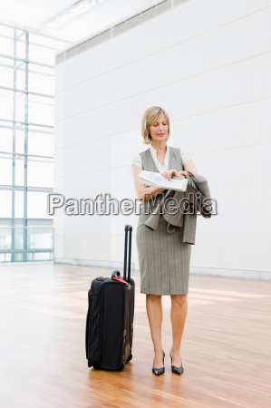 woman with suitcase looking at watch