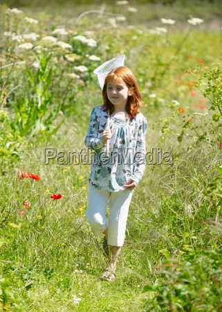 young girl in field with butterfly