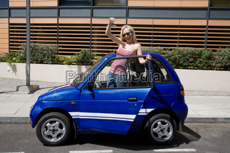 young woman waving by electric car