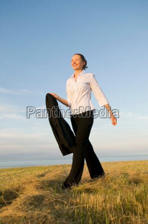 business woman walking across a field