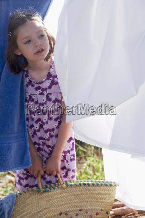 young girl looking through washing