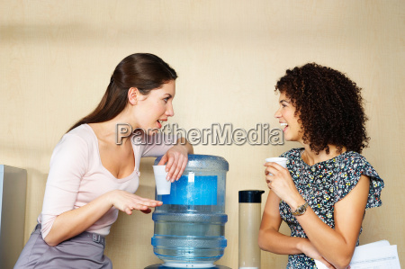two women are chatting by water