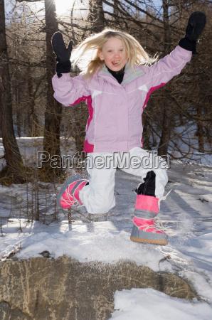 girl jumping wearing ski outfit